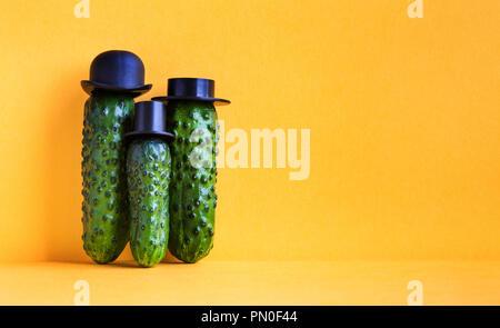 Komische grüne Gurken Familie auf gelben Hintergrund. Drei lustige Gemüse mit schwarzen altmodische Hüte. Creative Design Essen poster Vorlage. Platz kopieren - Stockfoto