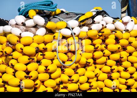 Gelbe schwimmt auf dem Stapel, die Fischernetze auf dem blauen Boot im Sommer Sonne, aus der Nähe. Angeln schwebt mit Seil Knoten angehäuft Verrechnung. - Stockfoto