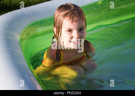 Lächelnde Mädchen sitzen in einem Kinder € ™ s Schwimmbad - Stockfoto