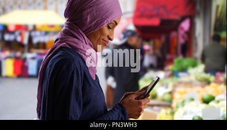 Schöne junge muslimische Frau sms mit Smartphone außerhalb - Stockfoto