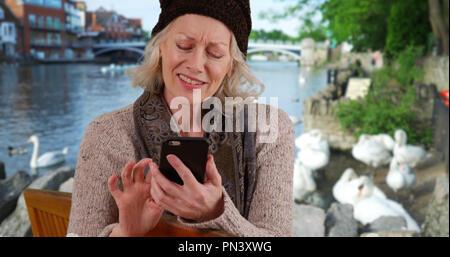 Ältere Frau auf parkbank am Fluss in Windsor auf Handy mit Schwänen - Stockfoto