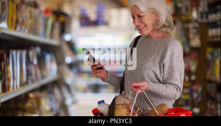 Gerne ältere Frau an Lebensmittelgeschäft gang Suchen mit Handy in der Hand - Stockfoto