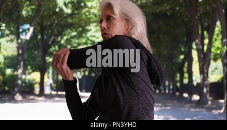Gesunde, aktive reife Frau Aufwärmen für im Park laufen - Stockfoto