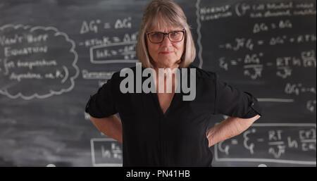 Alte ältere Frau Lehrerin mit ernsthaften Haltung vor der Tafel posing - Stockfoto