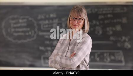 Zuversichtlich senior Frau Lehrerin mit verschränkten Armen stand vor der Tafel - Stockfoto