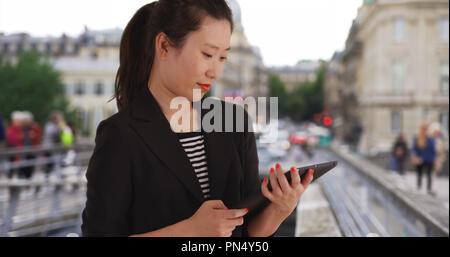 Freudige junge asiatische business lady mit handheld Tablet Computer in Europa - Stockfoto