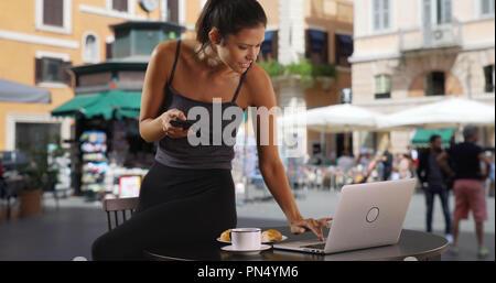 Hübsche Geschäftsfrau in Italien mit Kaffee und Gebäck texting und mit Laptop - Stockfoto