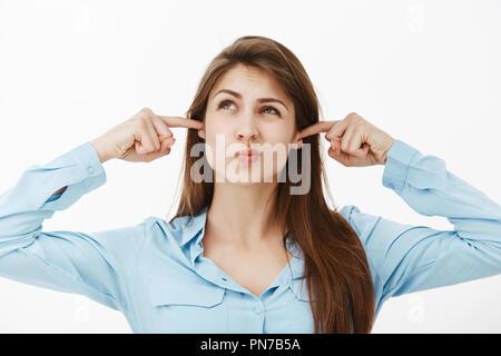 Übel lustig europäischen Mädchen in blau Bluse und runzelte die Stirn, die Ohren mit Zeigefinger, mit gefalteten Lippen, unzufrieden und verärgert, mit Lärm von oben gestört - Stockfoto