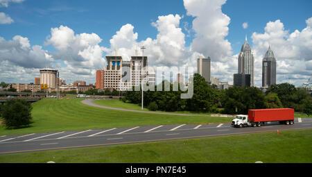 Ein LKW-Transport Shipping Container entspricht den Himmel hinter der Innenstadt von Mobile Alabama Skyline der Stadt. - Stockfoto
