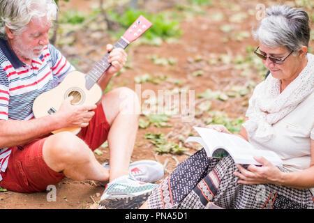 Paar Alternativen im Alter von älteren Reisenden bleiben oder sich in einen Weinberg mit dem Gepäck und spielen eine Ukulele, E-Gitarre und Lesen ein Papier - Stockfoto