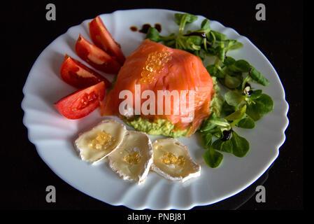 Weiße Platte mit gesunden Mahlzeit auf schwarzem Hintergrund, in der Mitte der Platte ist geräucherter Lachs um Avocado gewickelt; mit Fisch, Kaviar überstieg, Ziegenkäse - Stockfoto