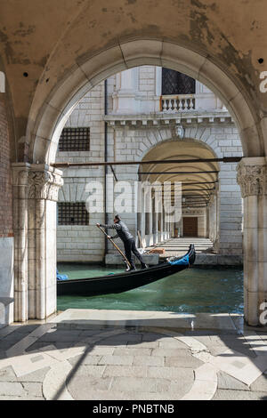 Venedig, Italien, 21. März 2018: Venezianische Gondoliere reiten Gondel durch die seitlichen schmalen Kanal in Venedig.