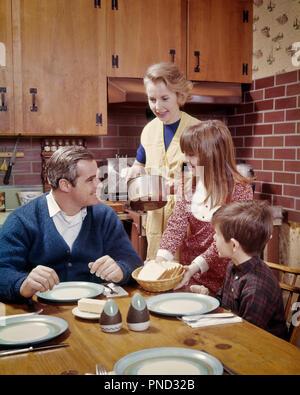 1960s 1970s Mutter ÜBER ZU DIENEN FAMILIE AM TISCH IN DER KÜCHE BEREIT ZU ESSEN - Kd 3124 PHT 001 HARS MANN SERVICE INDOOR VIER SPEISEN ESSEN DRINNEN NOSTALGISCHE PAAR 4 SUBURBAN FARBE BEZIEHUNG MÜTTER ALTE ZEIT BESETZT NOSTALGIE OLD FASHION 1 JUGENDLICHE BALANCE SICHERHEIT TEAMARBEIT SÖHNE FAMILIEN FREUDE LIFESTYLE PARENTING FEIER FRAUEN BEREIT BEZIEHUNG EHEMÄNNER GROWNUP GESUNDHEIT HOME LEBEN MIT HALBER LÄNGE TÖCHTER PERSONEN ERWACHSEN FÜRSORGLICHE MÄNNER VERTRAUEN VÄTER MANN UND FRAU MÄNNER UND FRAUEN väterlichen Elternteil und Kind Ehemänner und Ehefrauen HAUSWIRTSCHAFTSLEITERIN ELTERN UND KINDERN VATERSCHAFT MÜTTERLICHEN GLÜCK HAUSFRAUEN - Stockfoto