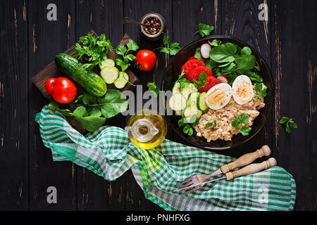 Gesunden Salat von frischem Gemüse - Tomaten, Gurken, Rettich, Ei, Rucola und haferflocken an der Schale. Diät essen. Flach. Ansicht von oben - Stockfoto