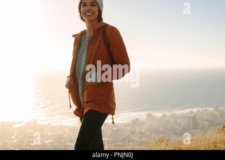 Portrait von lächelnden afrikanische Frauen tragen warme Kleidung auf. Junge Frau wandern in den Bergen an einem Wintertag. - Stockfoto