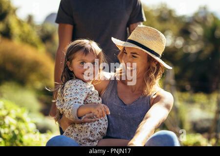 Süße kleine Mädchen mit ihrer Mutter sitzt auf schubkarren von einem Mann geschoben werden. Junge Familie Spaß im Freien in Ihrer Farm. - Stockfoto