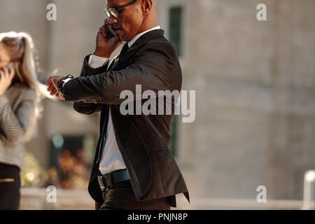 Mann auf seine Armbanduhr und Sprechen über Handy während der Fahrt in den Morgen. Geschäftsmann Kontrolle Zeit beim Gehen zu Offi - Stockfoto