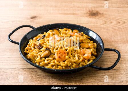 Traditionelle spanische fideua. Nudel Paella auf hölzernen Tisch - Stockfoto