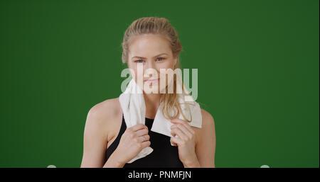 Hübsche sportliche Frau die Ruhestätte von Workout auf Green Screen - Stockfoto