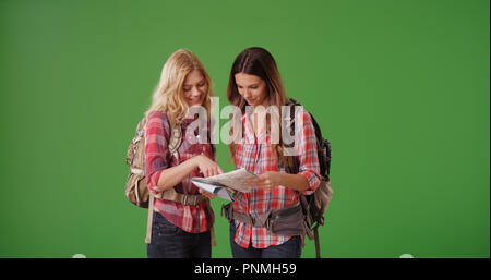 Paar weiße weibliche Wanderer auf Karte auf der Suche nach auf Green Screen verloren - Stockfoto