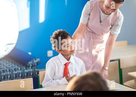 Lehrer Kind Hilfe bei den Hausaufgaben im Unterricht in der Schule