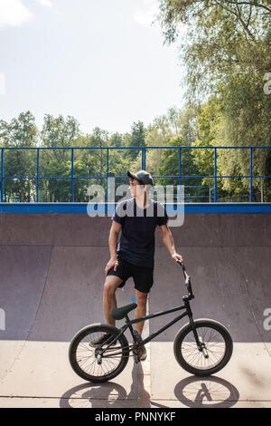 Junger Mann mit BMX Bike steht auf der Rampe. Street Kultur - Stockfoto