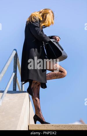 Teenager stehendes Mädchen auf der Straße suchen Sie etwas in Ihrer Handtasche Profil schwarzen Strumpfhosen - Stockfoto