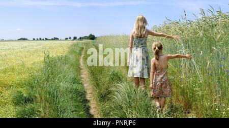 Junge Frau mit einem kleinen Mädchen zu Fuß auf der grünen Wiese, blauen Himmel im Hintergrund, Panorama - Stockfoto