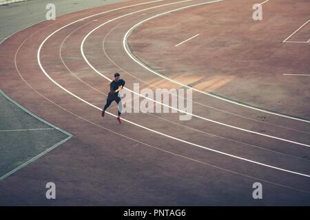 Ansicht von oben Athlet läuft auf der Laufstrecke. Runner sprinten auf roten Laufbahn im Stadion - Stockfoto