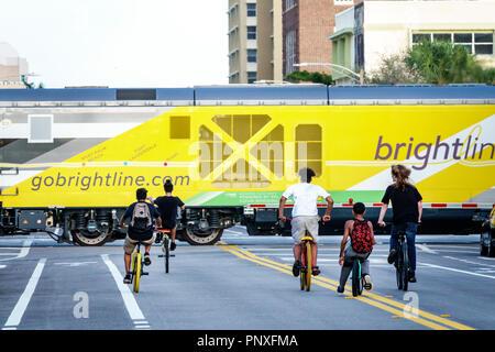 West Palm Beach Florida vorbei Brightline Personenzug junge Freunde Fahrräder Fahrräder reiten Middle Street - Stockfoto