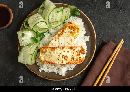 Tofu Steak mit Reis und Gurkensalat auf schwarzem Hintergrund, kopieren. Gesund vegan vegetarisch essen mit gebratenem Tofu gebraten Steak. - Stockfoto