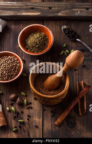 Indische Garam Masala Pulver mit ingridients auf hölzernen Hintergrund - Stockfoto