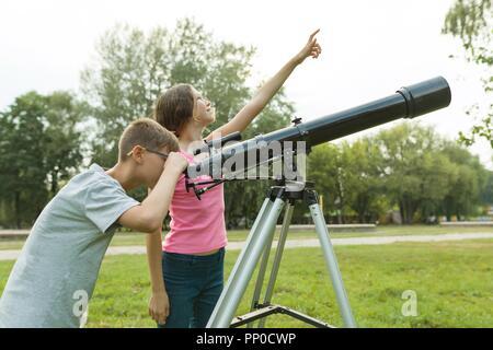 Kleiner junge schaut in himmel mit teleskop stockfoto bild