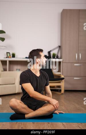Mann tun tiwst Yogastellungen, während zu Hause. Mobilität Training. - Stockfoto
