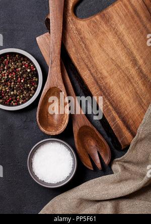 Vintage Küche Holz- Utensilien mit schneidebrett auf schwarzen Steintisch Hintergrund. Ansicht von oben. - Stockfoto