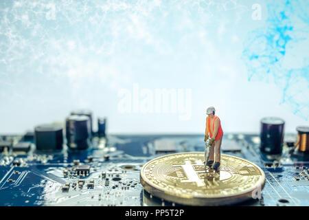 Miniatur Bauarbeiter stehen auf physischen Bitcoin, isolierte mining Konzept - Stockfoto