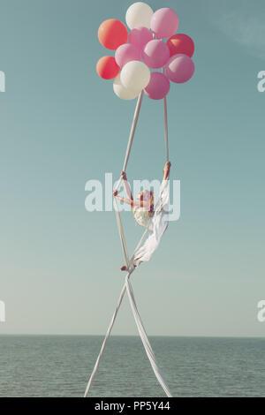 Frau gymnast fliegt auf Kugeln hoch in den Himmel und zeigt Garn. - Stockfoto