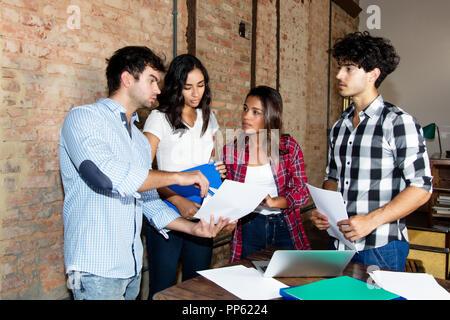 Gruppe von Geschäftsleuten von Start-up-Unternehmen in Freizeitkleidung in der Diskussion - Stockfoto