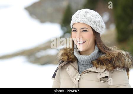 Gerne Frau posiert an der Kamera auf Winterurlaub in die schneebedeckten Berge - Stockfoto