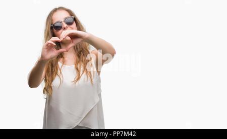 Junge blonde Frau mit Sonnenbrille in der Liebe mit Herz und mit Hand lächelnd. Romantische Konzept. - Stockfoto