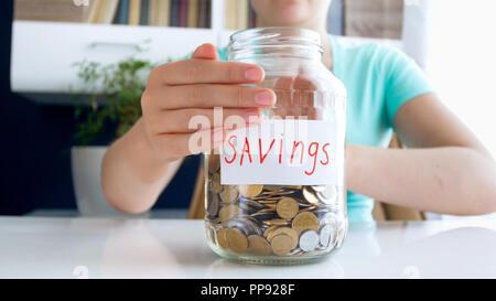 CLoseup Bild der Frau mit ihrem Geld zu sparen, in Glas Glas - Stockfoto
