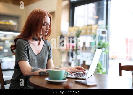 Red Head Mädchen mit Arm Tattoo, allein in einem Cafe, das Arbeiten mit einem Notebook, Handy und ein Laptop, Liverpool, Großbritannien - Stockfoto