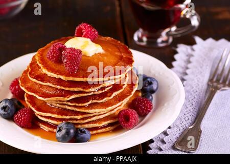 Pfannkuchen mit frischen Beeren und Ahornsirup auf hölzernen Tisch - Stockfoto