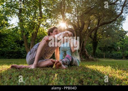 Junge Familie, Mutter, Vater und Kind Kind, sitzen in einem Gras im Park genießen einen schönen sonnigen Tag. - Stockfoto