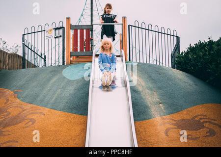 Blonde Mädchen spielen auf Folie im Spiel Park Stockfoto