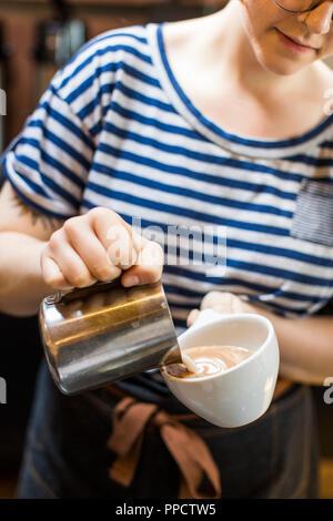 Den mittleren Abschnitt der weiblichen Barista erstellen Latte Art, Seattle, Washington, USA - Stockfoto
