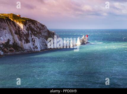 Ein Bruch in den Wolken beleuchtet die ikonischen Chalk stone Zinnen der Nadeln und dem 19. Jahrhundert Leuchtturm an der Küste Insel von Wight ein ist - Stockfoto
