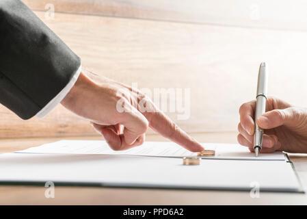 Männliche Hand drücken einen Ehering an eine weibliche Hand über die Scheidungspapiere unterzeichnen. Konzeptionelle der Scheidung oder Heirat. - Stockfoto