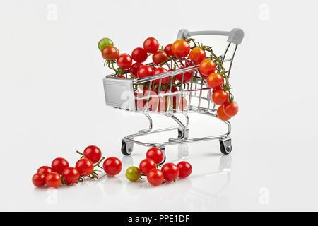 Mini Warenkorb voll mit Cherry Tomaten auf weißem Hintergrund. Platz kopieren - Stockfoto