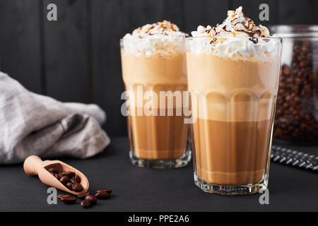 Iced Caramel latte Kaffee in einem großen Glas mit Schokolade Sirup und Sahne. Dunklen Hintergrund. - Stockfoto